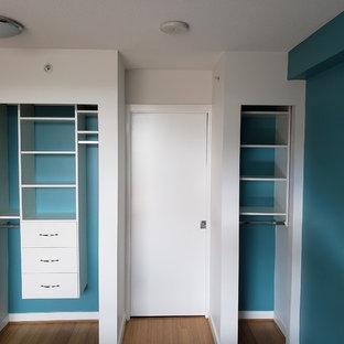 Foto de armario unisex, minimalista, pequeño, con armarios con paneles lisos, puertas de armario blancas, suelo laminado y suelo marrón