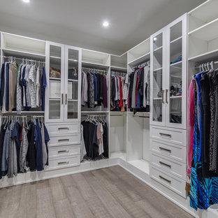 Diseño de armario vestidor unisex, actual, de tamaño medio, con armarios estilo shaker, puertas de armario marrones, suelo de madera clara y suelo gris