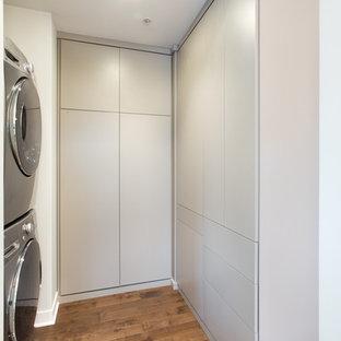 Foto de armario y vestidor unisex, actual, pequeño, con armarios con paneles lisos, puertas de armario grises y suelo de madera en tonos medios