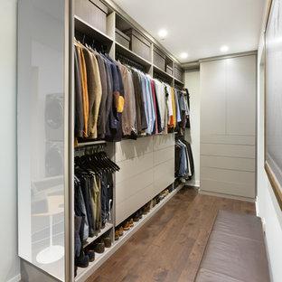 Diseño de armario y vestidor unisex, contemporáneo, pequeño, con armarios con paneles lisos, puertas de armario grises y suelo de madera en tonos medios