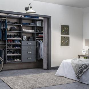 Cette photo montre un petit placard dressing tendance neutre avec des portes de placard grises, un placard sans porte, béton au sol et un sol beige.