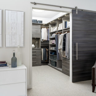 Walk-in closet - mid-sized transitional gender-neutral carpeted and beige floor walk-in closet idea in Charleston with flat-panel cabinets and brown cabinets