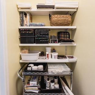 Modelo de armario vestidor clásico, pequeño, con armarios con paneles con relieve, puertas de armario de madera oscura, suelo laminado y suelo marrón