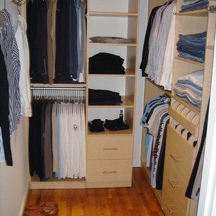 Diseño de armario vestidor de hombre, contemporáneo, de tamaño medio, con armarios con paneles lisos, puertas de armario de madera clara, suelo de madera en tonos medios y suelo marrón