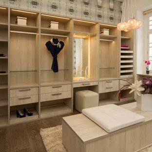 Modelo de armario vestidor unisex, contemporáneo, de tamaño medio, con armarios con paneles lisos, puertas de armario de madera clara y suelo de baldosas de cerámica