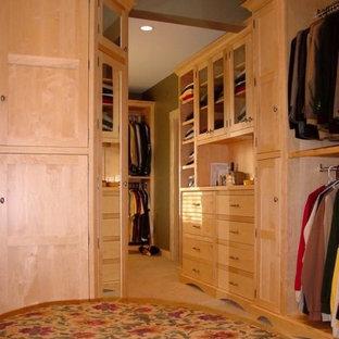 Ejemplo de armario vestidor unisex, tradicional, grande, con armarios tipo vitrina, puertas de armario de madera clara y moqueta