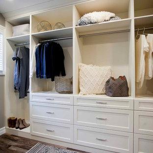 Inspiration för ett stort funkis walk-in-closet för könsneutrala, med öppna hyllor, vita skåp, mellanmörkt trägolv och brunt golv