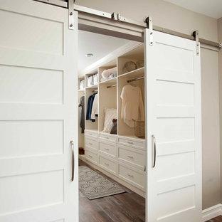 Diseño de armario vestidor unisex, clásico renovado, grande, con armarios abiertos, puertas de armario blancas, suelo de madera en tonos medios y suelo marrón