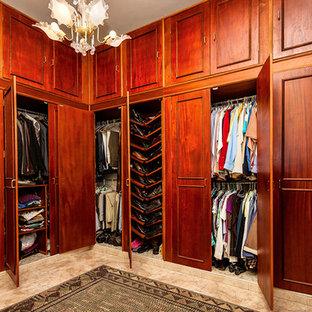 Foto de armario vestidor unisex, tradicional, grande, con armarios con paneles empotrados, puertas de armario de madera oscura, suelo de baldosas de cerámica y suelo marrón