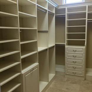 Inspiration for a medium sized traditional gender neutral walk-in wardrobe in Miami with raised-panel cabinets, white cabinets and travertine flooring.