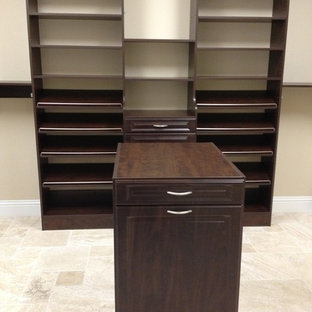 Inspiration for a large traditional gender neutral walk-in wardrobe in Miami with open cabinets, dark wood cabinets and travertine flooring.