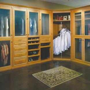 Ispirazione per una cabina armadio per uomo tradizionale di medie dimensioni con ante di vetro, ante in legno chiaro e pavimento in cemento