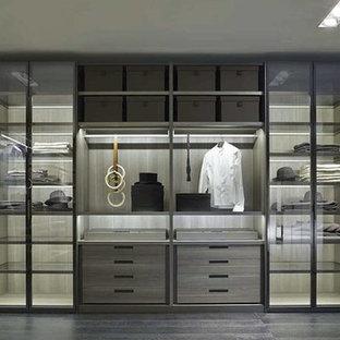 Immagine di grandi armadi e cabine armadio per uomo moderni con ante di vetro, ante in legno bruno e parquet scuro
