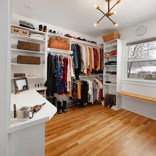 Foto de armario vestidor unisex, clásico renovado, de tamaño medio, con suelo de madera en tonos medios, armarios abiertos, puertas de armario blancas y suelo marrón