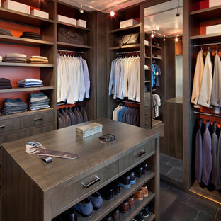 Design ideas for a large contemporary walk-in wardrobe for men in New York with flat-panel cabinets, dark wood cabinets and slate flooring.