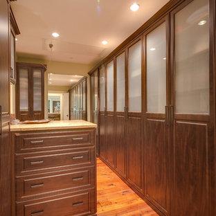 Imagen de armario vestidor unisex, de estilo de casa de campo, grande, con armarios con paneles con relieve, puertas de armario de madera en tonos medios y suelo de madera en tonos medios