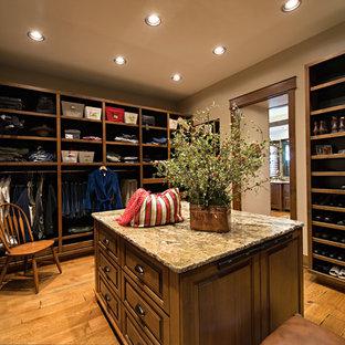 Foto de armario vestidor unisex, de estilo americano, extra grande, con puertas de armario de madera oscura, suelo de madera en tonos medios y armarios con paneles con relieve