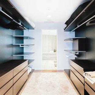 Diseño de armario vestidor unisex, moderno, grande, con armarios con paneles lisos, puertas de armario de madera en tonos medios, suelo de contrachapado y suelo marrón