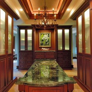 Cette photo montre un dressing room exotique avec des portes de placard en bois sombre et un placard avec porte à panneau surélevé.