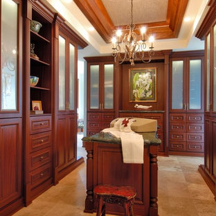 Design ideas for a traditional dressing room in Hawaii with dark wood cabinets and travertine flooring.