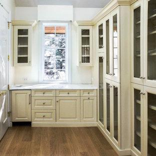 Imagen de vestidor tradicional, de tamaño medio, con armarios con paneles con relieve, puertas de armario amarillas y suelo de madera clara