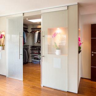 Modelo de vestidor unisex, contemporáneo, grande, con armarios abiertos, puertas de armario de madera en tonos medios y suelo de madera en tonos medios