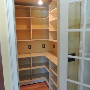 Imagen de armario vestidor tradicional, de tamaño medio, con puertas de armario beige y suelo de madera clara