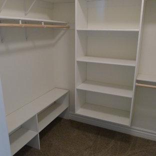Immagine di una cabina armadio unisex tradizionale di medie dimensioni con nessun'anta, ante bianche e moquette