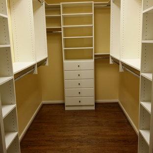 Ejemplo de armario vestidor de mujer, tradicional, de tamaño medio, con armarios con paneles lisos, puertas de armario blancas y suelo de madera oscura