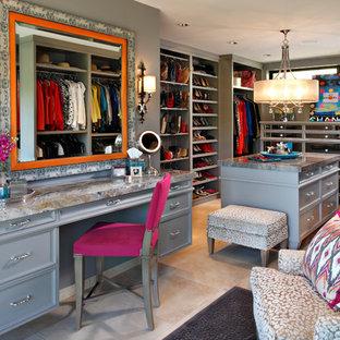 Cette photo montre un grand dressing room chic pour une femme avec un placard avec porte à panneau encastré, des portes de placard grises et un sol en travertin.