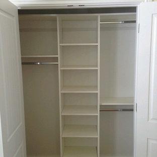 Modelo de armario vestidor unisex, clásico, de tamaño medio, con puertas de armario blancas, armarios abiertos y suelo de madera oscura