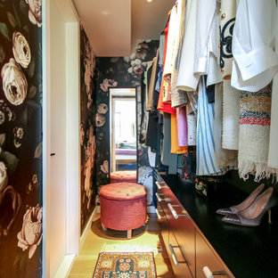Ispirazione per una piccola cabina armadio per donna boho chic con ante lisce, ante nere, parquet chiaro e pavimento marrone