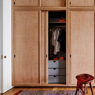 Large midcentury storage and wardrobe in New York with light hardwood floors and brown floor.