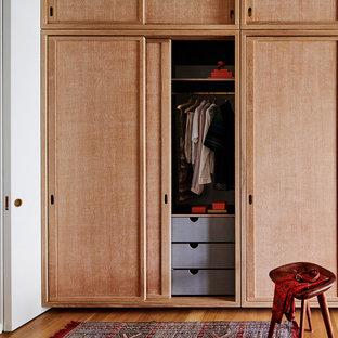 Idées déco pour un grand dressing et rangement rétro avec un sol en bois clair et un sol marron.