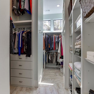 Photo of a large traditional gender neutral dressing room in Houston with flat-panel cabinets, white cabinets, travertine flooring and beige floors.