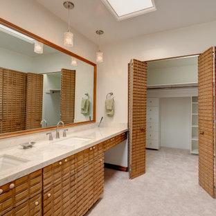 ロサンゼルスの大きい男女兼用ミッドセンチュリースタイルのおしゃれなフィッティングルーム (中間色木目調キャビネット、カーペット敷き、ベージュの床) の写真