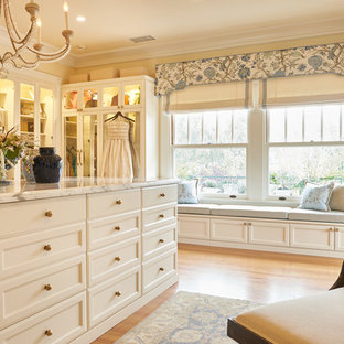 Walk-in closet - traditional women's medium tone wood floor and brown floor walk-in closet idea in Los Angeles with recessed-panel cabinets and white cabinets