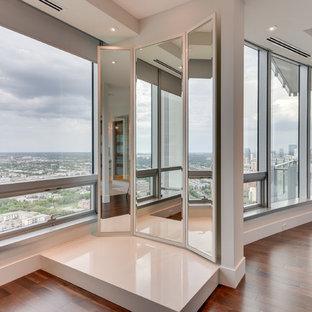 Foto di un'ampia cabina armadio unisex design con pavimento in legno massello medio