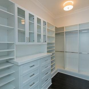 Foto de armario vestidor unisex, clásico, grande, con armarios estilo shaker, puertas de armario blancas y suelo de madera oscura