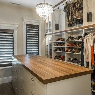 Ejemplo de vestidor unisex, clásico, grande, con moqueta, armarios tipo vitrina, puertas de armario de madera clara y suelo marrón