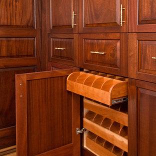 Idee per un ampio spazio per vestirsi unisex chic con ante con bugna sagomata, ante in legno bruno e pavimento in legno massello medio