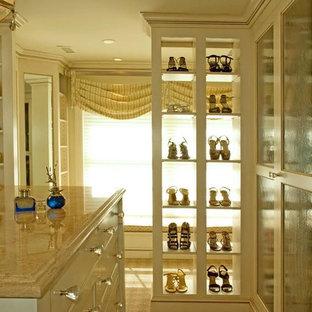 Foto de armario vestidor de mujer, grande, con armarios tipo vitrina, puertas de armario beige y moqueta