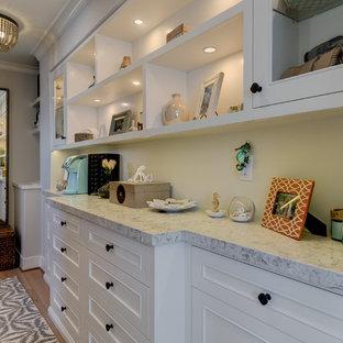 Diseño de armario vestidor de mujer, costero, de tamaño medio, con armarios con paneles con relieve, puertas de armario blancas, suelo de madera en tonos medios y suelo beige
