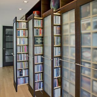 Example of a trendy gender-neutral light wood floor reach-in closet design in Phoenix with glass-front cabinets and dark wood cabinets