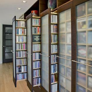 Immagine di un armadio o armadio a muro unisex contemporaneo con ante di vetro, ante in legno bruno e parquet chiaro