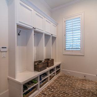 中くらいの男女兼用カントリー風おしゃれなウォークインクローゼット (白いキャビネット、レンガの床) の写真