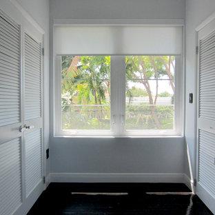 Foto de vestidor unisex, ecléctico, grande, con armarios con puertas mallorquinas, puertas de armario blancas y suelo de madera oscura