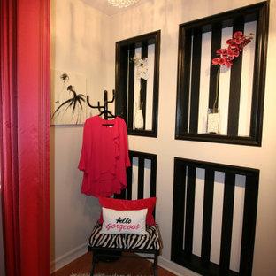 Ejemplo de vestidor unisex, clásico renovado, pequeño, con suelo laminado y suelo naranja
