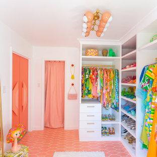 ニューヨークの広い女性用ミッドセンチュリースタイルのおしゃれなウォークインクローゼット (白いキャビネット、セラミックタイルの床、ピンクの床) の写真