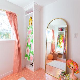 Aménagement d'un grand dressing rétro pour une femme avec des portes de placard blanches, un sol en carrelage de céramique et un sol rose.